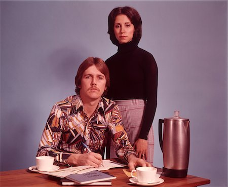 1970s SERIOUS COUPLE HUSBAND SITTING WEARING LOUD PRINT SHIRT WRITING FAMILY BUDGET WIFE STANDING BEHIND COFFEE POT ON DESK Stock Photo - Rights-Managed, Code: 846-05647405