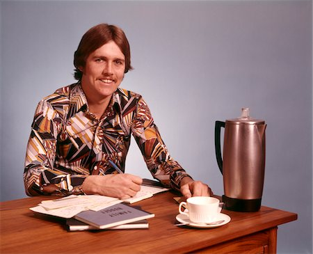 1970s YOUNG MAN MUSTACHE LOUD PRINT SHIRT DESK EMPTY COFFEE CUP POT WORKING ON FAMILY BUDGET LOOKING AT CAMERA Stock Photo - Rights-Managed, Code: 846-05647406