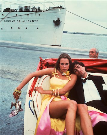 1970s - 1980s COUPLE IN OPEN HANSOM CAB MAN TUXEDO ASLEEP WOMAN ANGRY ON DOCK CRUISE SHIP BYSTANDER Stock Photo - Rights-Managed, Code: 846-05647425