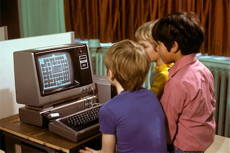 1980s 3 ELEMENTARY SCHOOL BOYS OPERATING EARLY RADIO SHACK TRS80 COMPUTER PLAYING GAME Stock Photo - Rights-Managed, Code: 846-05647435