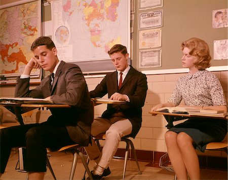 1960s 3 COLLEGE HIGH SCHOOL STUDENTS SITTING DESK CHAIRS READING STUDYING CLASSROOM Stock Photo - Rights-Managed, Code: 846-05647431