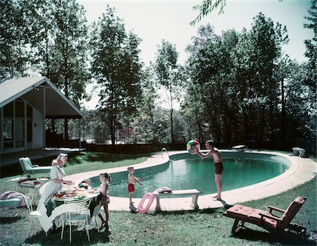 1950s FAMILY MAN WOMAN SON DAUGHTER BACKYARD KIDNEY SHAPE SWIMMING POOL PICNIC FOOD BEACH BALL HOUSE TREES SUMMER Stock Photo - Rights-Managed, Code: 846-05647505