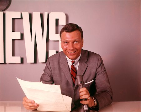 1960s SMILING BROADCAST REPORTER NEWSMAN ANNOUNCER AT NEWS DESK HOLDING MICROPHONE PAPERS READING REPORT Stock Photo - Rights-Managed, Code: 846-05647531