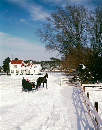 1960s MAN WOMAN COUPLE IN ONE HORSE DRAWN OPEN SLEIGH APPROACHING SNOWY WHITE FARM HOUSE Stock Photo - Rights-Managed, Code: 846-05647571