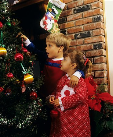 1980s BOY GIRL WEARING PAJAMAS PUTTING ORNAMENTS ON CHRISTMAS TREE Stock Photo - Rights-Managed, Code: 846-05647587