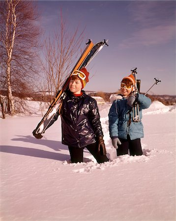1970s SMILING YOUNG BOY AND GIRL WALKING IN DEEP SNOW UP TO KNEES CARRYING SKIS AND SKI POLES Stock Photo - Rights-Managed, Code: 846-05647580