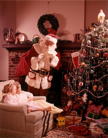 1960s SANTA LOOKING DOWN ON TWO CHILDREN BOY GIRL ASLEEP IN CHAIR BY FIREPLACE CHRISTMAS TREE Stock Photo - Rights-Managed, Code: 846-05647602