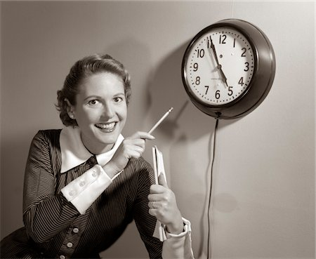 five - 1950s SMILING WOMAN STENOGRAPHER OFFICE WORKER HOLDING STENO PAD POINTING WITH PENCIL TO CLOCK 5 MINUTES TILL QUITTING TIME Stock Photo - Rights-Managed, Code: 846-05647798