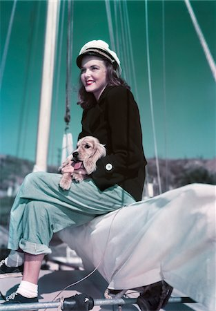 sports and sailing - 1940s - 1950s SMILING WOMAN WEARING SAILING YACHTING OUTFIT SITTING ON EDGE OF SAILBOAT HOLDING PUPPY IN LAP Stock Photo - Rights-Managed, Code: 846-05647804