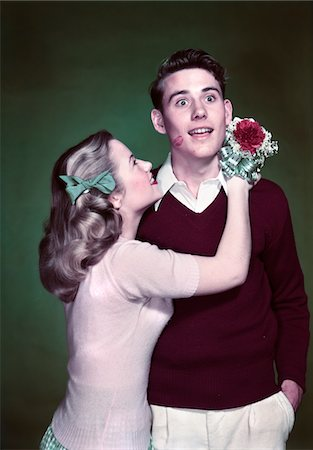 1940s - 1950s TEEN COUPLE GIRL HOLDING NOSEGAY BOUQUET HUGGING SURPRISED BOY LIPSTICK KISS ON CHEEK Stock Photo - Rights-Managed, Code: 846-05647818