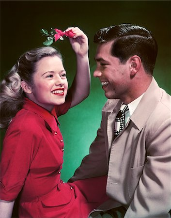 1950s SMILING TEEN COUPLE GIRL HOLDING CHRISTMAS MISTLETOE OVER HEAD Stock Photo - Rights-Managed, Code: 846-05647830