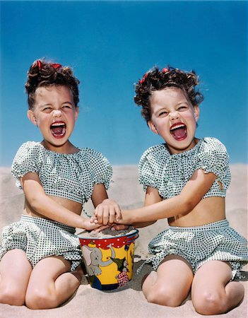 1940s - 1950s SMILING LAUGHING TWIN GIRLS WEARING CHECKERED TWO PIECE BATHING SUITS PLAYING ON SANDY BEACH Stock Photo - Rights-Managed, Code: 846-05647831