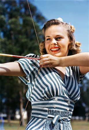 1940s - 1950s SMILING TEEN GIRL ARCHER WEARING BLUE AND WHITE STRIPED DRESS SHOOTING AIMING BOW AND ARROW Stock Photo - Rights-Managed, Code: 846-05647847