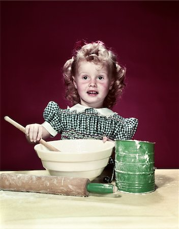 1940s GIRL WEARING CHECKED DRESS MIXING INGREDIENTS IN BOWL WITH WOODEN SPOON Stock Photo - Rights-Managed, Code: 846-05647840