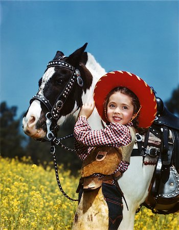 1940s - 1950s SMILING GIRL WEARING COWGIRL OUTFIT COWBOY HAT PETTING BLACK AND WHITE PONY Stock Photo - Rights-Managed, Code: 846-05647856