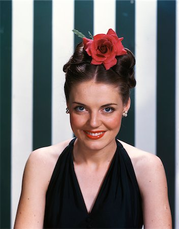 1940s - 1950s PORTRAIT SMILING BRUNETTE TEENAGE GIRL WEARING BLACK EVENING GOWN LARGE RED ROSE IN HAIR LOOKING AT CAMERA Stock Photo - Rights-Managed, Code: 846-05647861