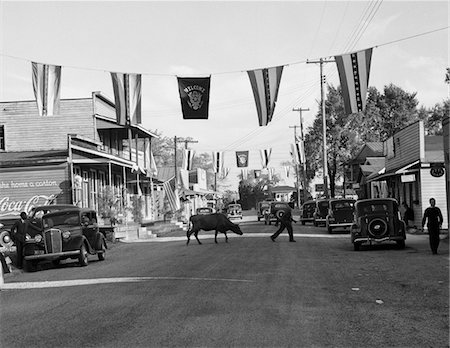 1930s MAIN STREET SMALL TOWN WITH FLAGS FLYING & COW CROSSING STREET Stock Photo - Rights-Managed, Code: 846-05647972