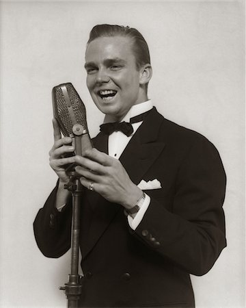 1920s - 1930s SMILING MAN RADIO SINGER ENTERTAINER CROONER IN TUXEDO SINGING INTO MICROPHONE Stock Photo - Rights-Managed, Code: 846-05648047