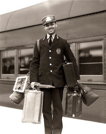 1930s - 1940s PORTRAIT SMILING AFRICAN AMERICAN MAN RED CAP PORTER CARRYING LUGGAGE BAGS SUITCASES PASSENGER RAILROAD TRAIN Stock Photo - Rights-Managed, Code: 846-05648087