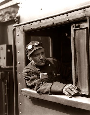 steam engine - 1920s - 1930s - 1940s RAILROAD TRAIN ENGINEER LOOKING OUT WINDOW OF LOCOMOTIVE CAB DRIVING THE STEAM ENGINE Stock Photo - Rights-Managed, Code: 846-05648089