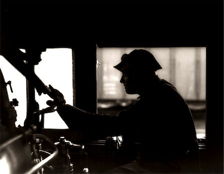 silhouette black and white - 1920s - 1930s - 1940s SILHOUETTE TRAIN ENGINEER AT CONTROLS IN LOCOMOTIVE CAB OF RAILROAD STEAM ENGINE Stock Photo - Rights-Managed, Code: 846-05648090