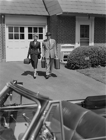 1950s COUPLE CARRYING LUGGAGE WALKING TOWARDS CONVERTIBLE CAR IN DRIVEWAY Stock Photo - Rights-Managed, Code: 846-05648112