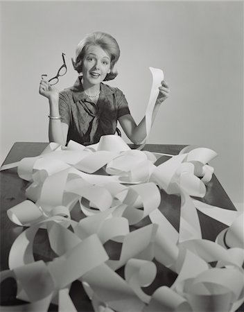 secretary desk - 1960s WOMAN HOLDING EYEGLASSES AND END OF EXTREMELY LONG TAPE FROM OFFICE MACHINE Stock Photo - Rights-Managed, Code: 846-05648160