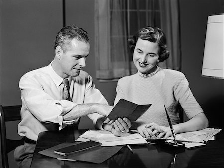 1950s COUPLE MAN WOMAN SMILING LOOKING AT BANKING SAVINGS PASSBOOK AT HOME DESK Stock Photo - Rights-Managed, Code: 846-05648214