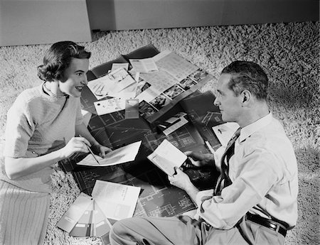 1950s COUPLE MAN WOMAN SITTING FLOOR LOOKING AT PLANS FOR NEW HOUSE Stock Photo - Rights-Managed, Code: 846-05648223