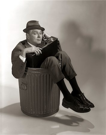 1960s SYMBOLIC BUSINESSMAN IN SUIT AND HAT HOLDING BRIEFCASE DUMPED FIRED MADE REDUNDANT LAID OFF UNEMPLOYED SITTING IN TRASH CAN Stock Photo - Rights-Managed, Code: 846-05648234
