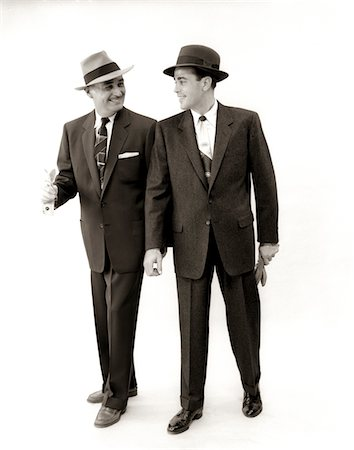 1950s TWO MEN SALESMAN BUSINESSMAN BUSINESS SUIT TIE HAT SMILING WALKING TALKING SIDE BY SIDE Stock Photo - Rights-Managed, Code: 846-05648314
