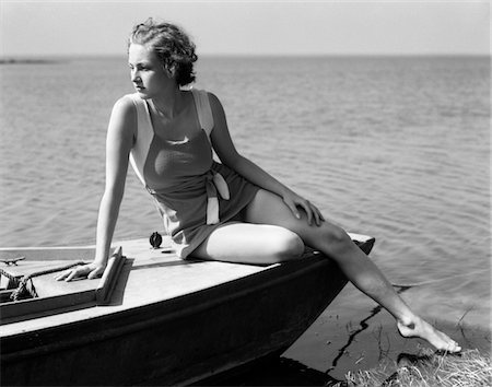 1930s WOMAN WEARING ONE PIECE BATHING SUIT SITTING ON EDGE OF BOAT Stock Photo - Rights-Managed, Code: 846-05648328