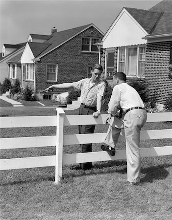 1950s 2 MEN NEIGHBORS TALKING OVER WHITE WOODEN FENCE BETWEEN SUBURBAN HOUSES Stock Photo - Rights-Managed, Code: 846-05648348
