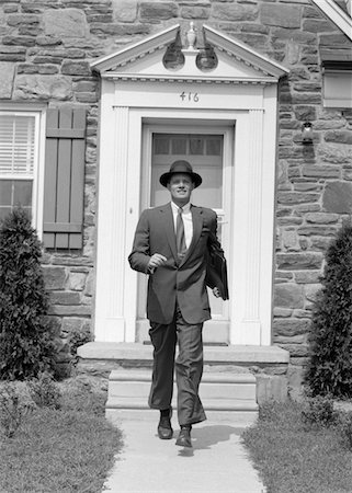 1950s MAN SMILING BUSINESSMAN PROUD LOOK OF SATISFACTION WALKING OUT SUBURBAN HOUSE FRONT DOOR WEARING HAT CARRYING BRIEFCASE Stock Photo - Rights-Managed, Code: 846-05648356