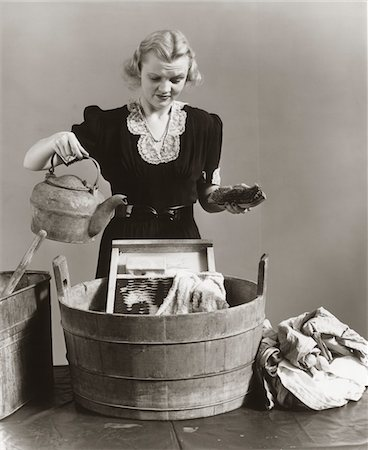 1940s DISPLEASED HOUSEWIFE POURING WATER FROM KETTLE INTO BUCKET WITH WASHBOARD & TOWEL Stock Photo - Rights-Managed, Code: 846-05648365