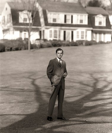 1950s MAN UPSCALE BUSINESSMAN EXECUTIVE IN GRAY FLANNEL SUIT AND TIE STANDING ON SUBURBAN HOME LAWN Stock Photo - Rights-Managed, Code: 846-05648361