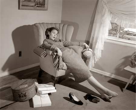1950s EXHAUSTED FEMALE SLUMPED IN CHAIR WITH SHOES OFF AFTER SHOPPING Stock Photo - Rights-Managed, Code: 846-05648375