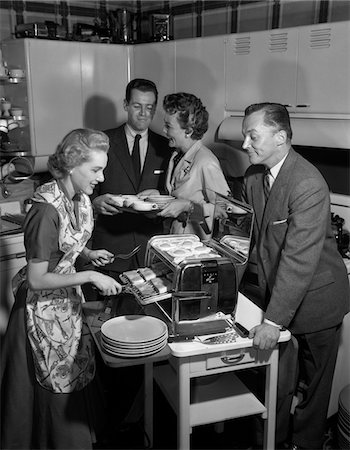 simsearch:846-02793283,k - 1950s 2 COUPLES IN KITCHEN WOMAN COOKING HAM & EGGS IN CHROME BROILER Stock Photo - Rights-Managed, Code: 846-05648384