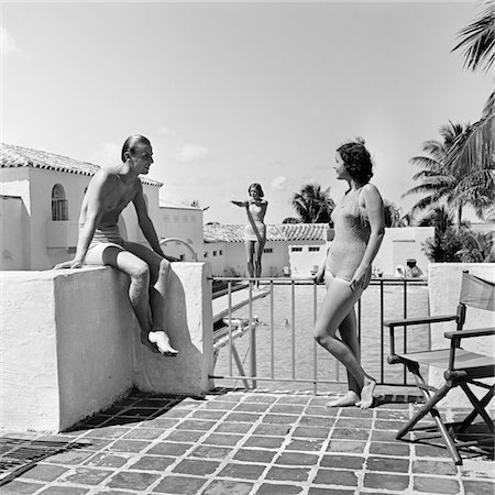 1930s MAN WOMAN WEARING BATHING SUITS ON TERRACE OVERLOOKING SWIMMING POOL WOMAN ON DIVING BOARD Stock Photo - Rights-Managed, Code: 846-05648421