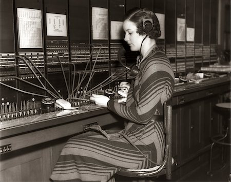 1930s WOMAN TELEPHONE OPERATOR SITTING AT LARGE MANUAL SWITCHBOARD DIRECTING CALLS Stock Photo - Rights-Managed, Code: 846-05648439