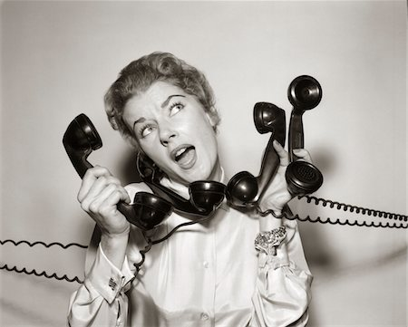 1950s - 1960s OVERWHELMED STRESSED WOMAN HOLDING ANSWERING FOUR BLACK TELEPHONE PHONE RECEIVERS AT ONE TIME Stock Photo - Rights-Managed, Code: 846-05648444