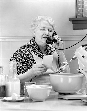 1940s WOMAN GRANDMOTHER HOUSEWIFE COOK IN KITCHEN WEARING APRON WITH FOOD MIXER READING INGREDIENTS LIST TALKING ON TELEPHONE Stock Photo - Rights-Managed, Code: 846-05648484