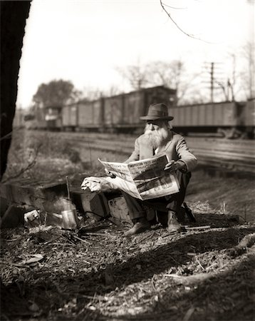 1930s HOBO SITTING BY RAILROAD TRACK READING NEWSPAPER DURING GREAT DEPRESSION Stock Photo - Rights-Managed, Code: 846-05648511