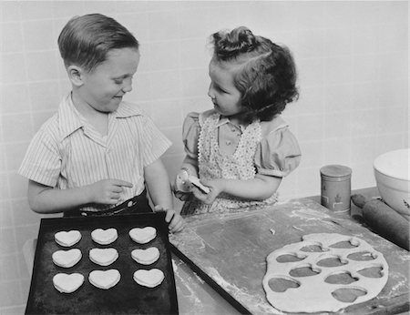 1940s YOUNG SMILING GIRL AND BOY BAKING HEART SHAPED VALENTINE COOKIES Stock Photo - Rights-Managed, Code: 846-05648512