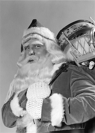 1940s PORTRAIT OF SMILING SANTA CLAUS WITH A SACK FOR OF TOY PRESENTS SLUNG OVER HIS SHOULDER LOOKING AT CAMERA Stock Photo - Rights-Managed, Code: 846-05648527
