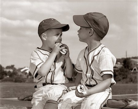 1960s LITTLE LEAGUE BASEBALL BOYS IN CAPS AND UNIFORMS EATING HOT DOGS Stock Photo - Rights-Managed, Code: 846-06111777