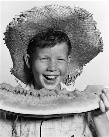 1940s 1950s FRECKLE-FACED BOY WEARING STRAW HAT EATING LARGE WEDGE OF WATERMELON LOOKING AT CAMERA Stock Photo - Rights-Managed, Code: 846-06111794
