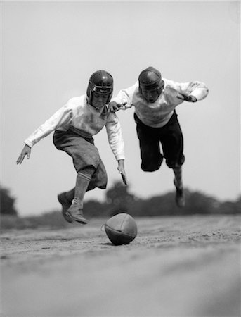 1930s PAIR OF BOYS IN KNICKERS & LEATHER HELMETS RACING TO DIVE ON FOOTBALL Stock Photo - Rights-Managed, Code: 846-06111798