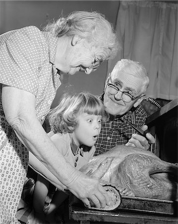 1950s 1960s EXCITED LITTLE GIRL GRANDDAUGHTER WITH GRANDPARENTS WATCHING ROAST TURKEY COMING OUT OF OVEN Stock Photo - Rights-Managed, Code: 846-06111801