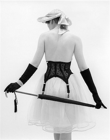 1950s BACK OF TOPLESS WOMAN WEARING HAT AND FULL LENGTH GLOVES PEARL BRACELET GIRDLE OVER CRINOLINE SKIRT PARASOL BEHIND BACK Stock Photo - Rights-Managed, Code: 846-06111802